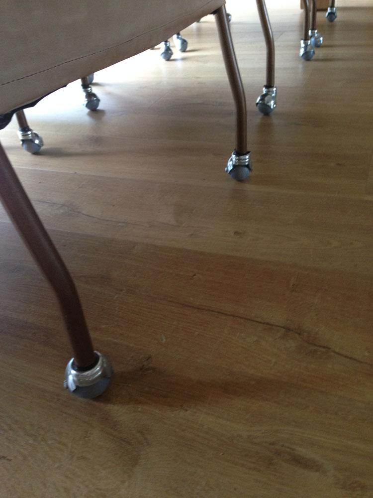 Stoelwieltjes onder een stoel gemonteerd